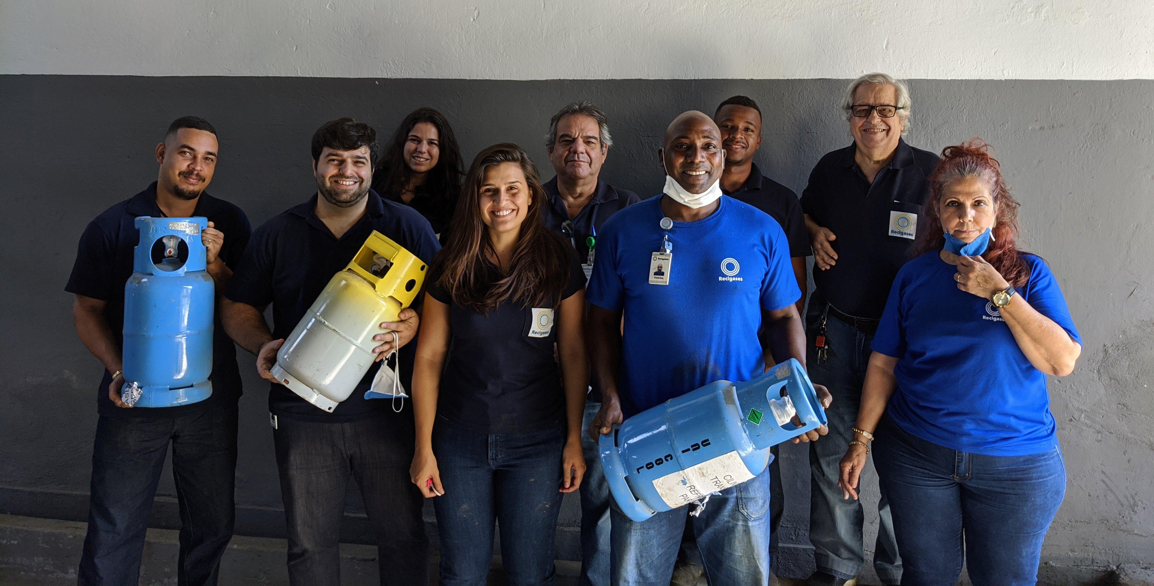 A foto está composta por 09 colaboradores olhando para a câmera e sorrindo. Dentre esses, três colaboradores estão segurando cilindros de gás refrigerantes.